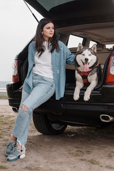 Front view of woman with husky dog traveling by car
