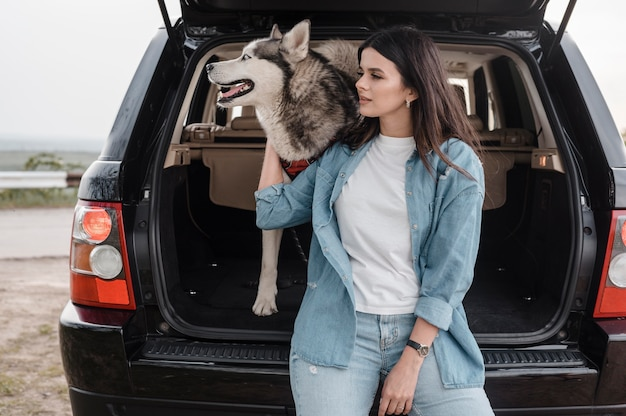 Front view of woman with husky traveling by car