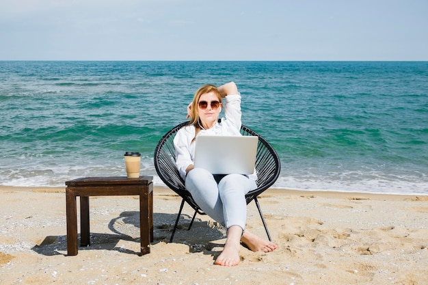 Front view of woman with laptop working at the beach with cup of coffee