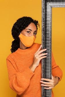 Vista frontale della donna con la maschera che tiene il telaio