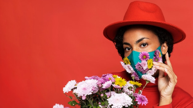 Front view of woman with mask posing with flowers