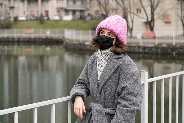 Vista frontale della donna con mascherina medica nella città vicino al lago