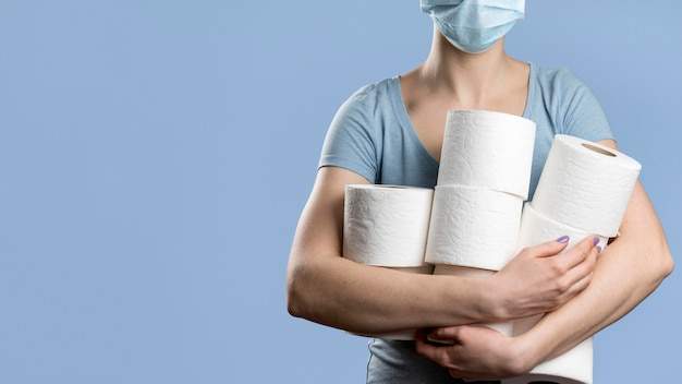 Front view of woman with medical mask holding multiple toilet paper rolls