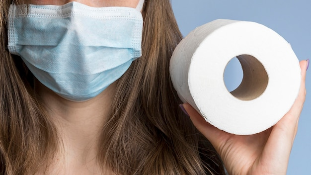 Front view of woman with medical mask holding toilet paper