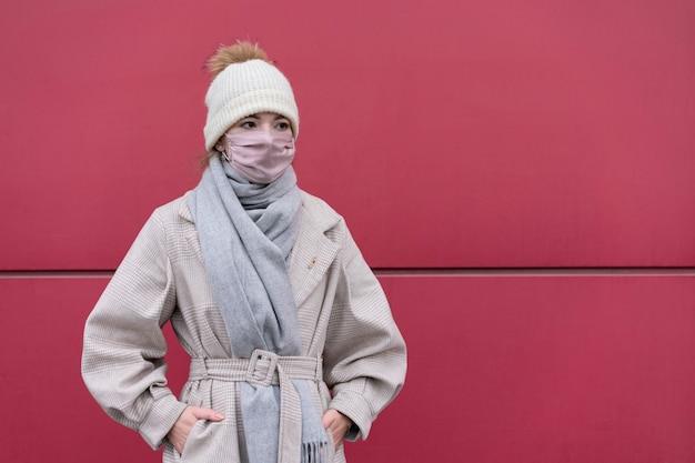 Vista frontale della donna con mascherina medica all'aperto e copia spazio