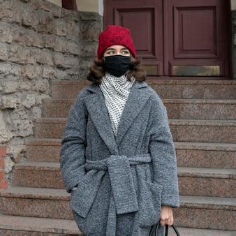 Vista frontale della donna con mascherina medica all'aperto