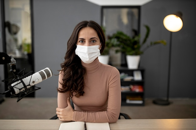 Vista frontale della donna con una mascherina medica in uno studio radiofonico