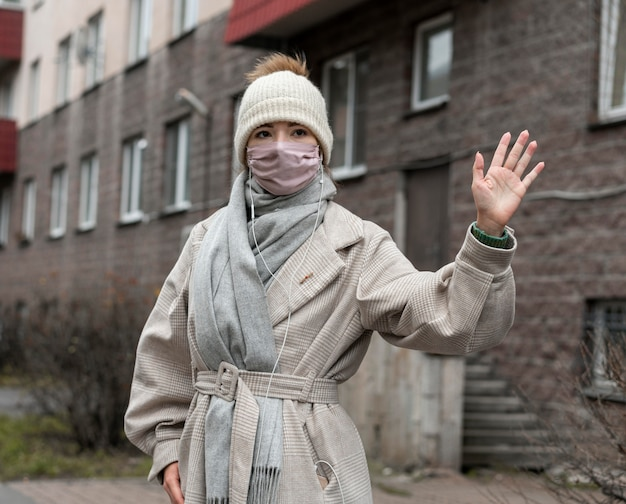 Vista frontale della donna con maschera medica sventolando