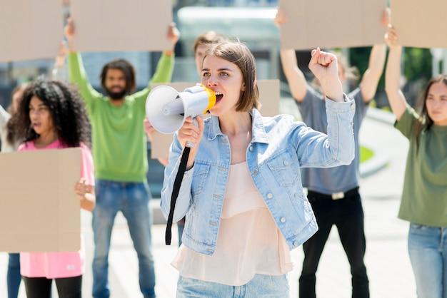通りで抗議しているメガホンを持つ正面女性