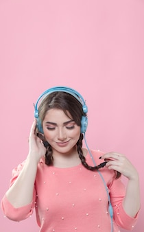 Front view of woman with ponytails listening to music on headphones