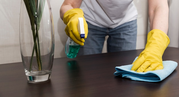Front view of woman with rubber gloves cleaning the table