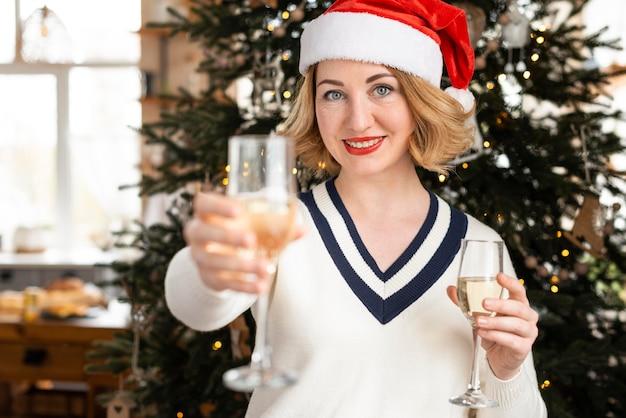 Вид спереди женщина в шляпе санта-клауса, держащая бокал шампанского