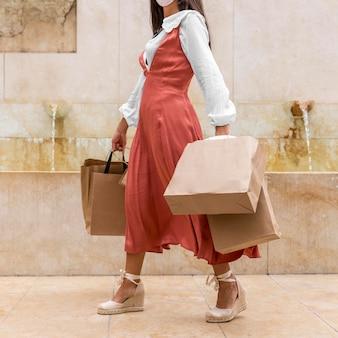 Vista frontale della donna con le borse della spesa