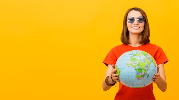 Front view of woman with sunglasses holding globe with copy space