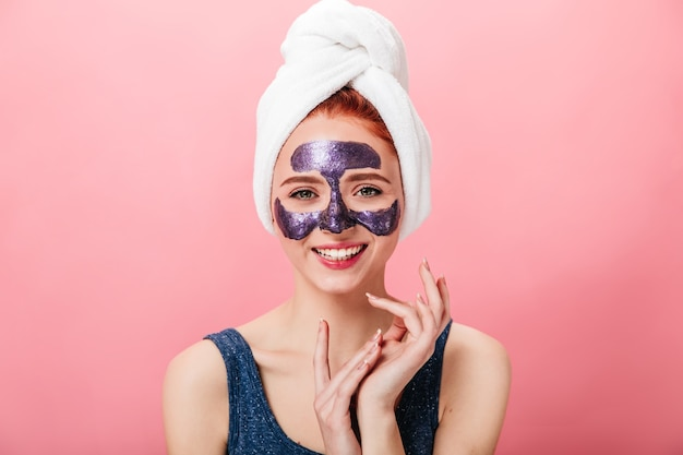 Front view of woman with towel and face mask. smiling girl doing skincare routine isolated on pink background.