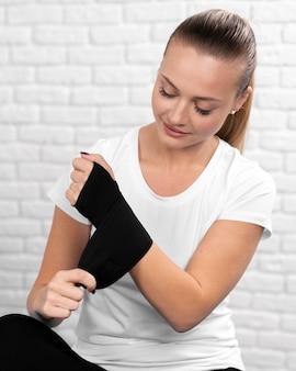 Vista frontale della donna con polso avvolto in fisioterapia
