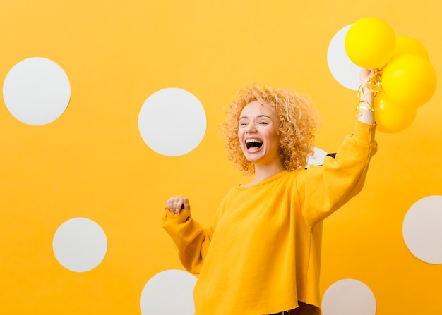 Vista frontale della donna con palloncini gialli