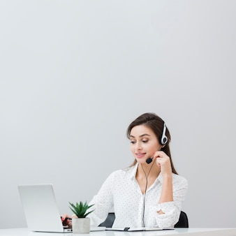 Front view of woman working at desk while wearing headset and looking at laptop
