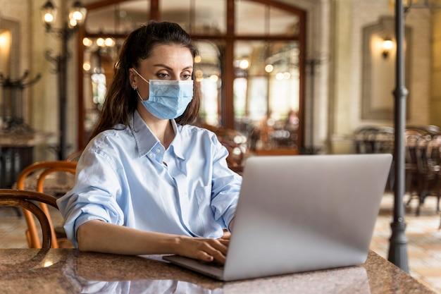 Donna di vista frontale che lavora all'interno mentre indossa una maschera facciale