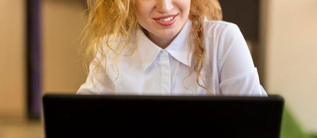 Вид спереди женщина, работающая на своем ноутбуке