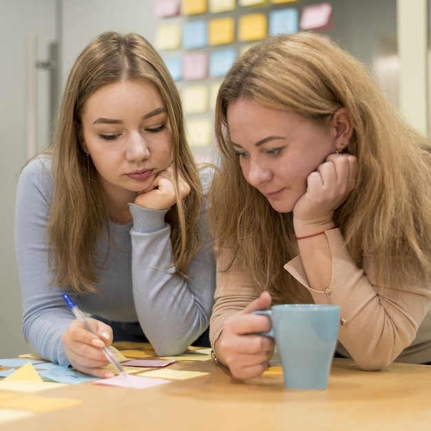 Vista frontale delle idee di scrittura della donna sulle note appiccicose all'ufficio