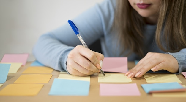 Front view of woman writing on sticky notes at the office