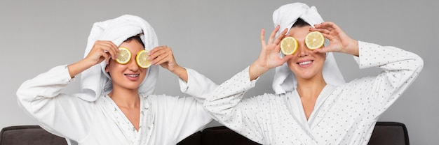 Front view of women in bathrobes and towels holding lemon slices over eyes