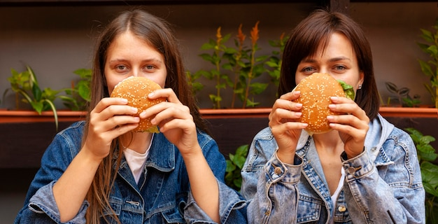 Front view of women covering their faces with burgers
