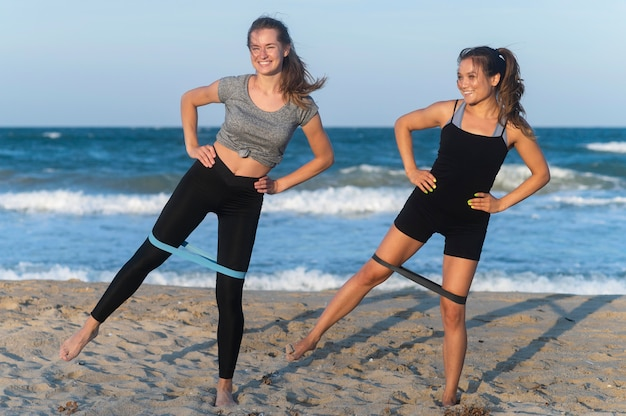 Front view of women exercising on the beach