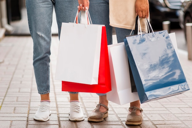 Vista frontale delle donne che tengono i sacchetti della spesa sulla strada