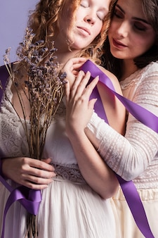 Front view of women hugging each other and holding lavender and ribbon