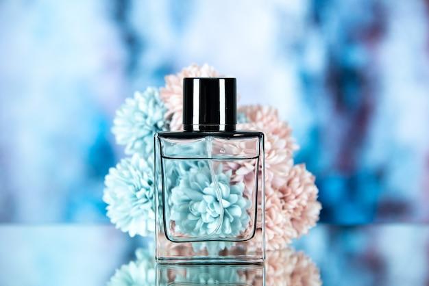 Vista frontale dei fiori della bottiglia di profumo delle donne su azzurro sfocato