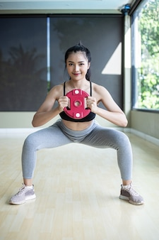 Front view of women in sports uniforms, pretending to squat and hold dumbbells while standing at the gym.