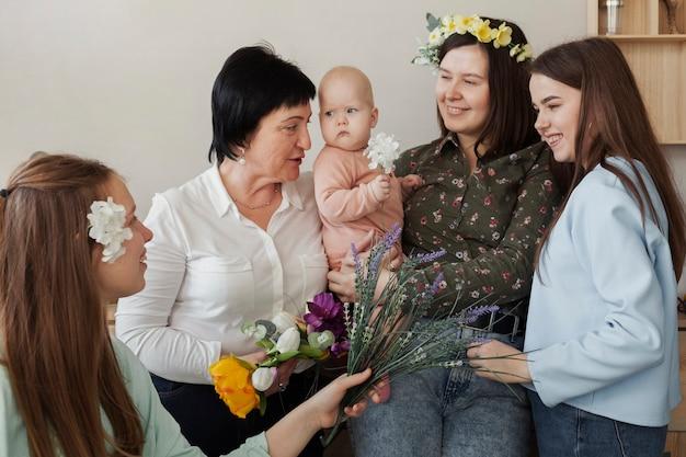 Вид спереди женщины с ребенком и цветами