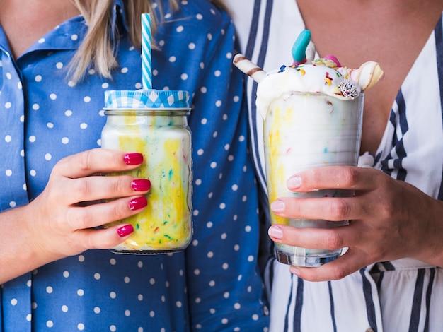 Front view of womens holing milkshake glasses