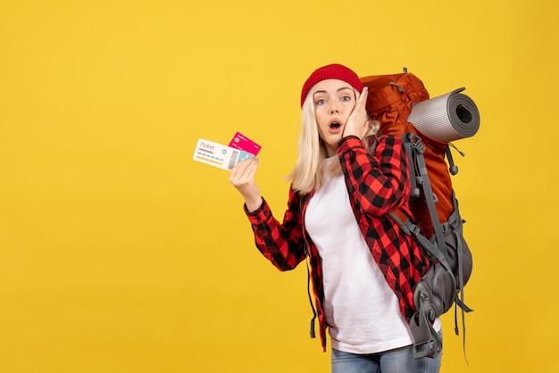 正面図は、カードと旅行チケットを保持している彼女のバックパックを持つブロンドの女の子を不思議に思った