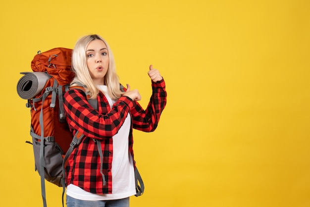 Front view wondered blonde woman with her backpack pointing with fingers behind