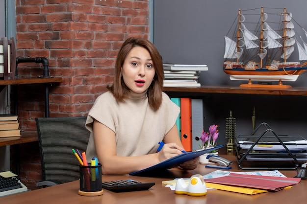 Vista frontale della donna d'affari meravigliata che controlla i documenti seduta al muro