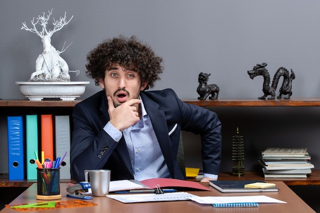 Front view of wondered businessman putting hand on his chin sitting at the desk in office