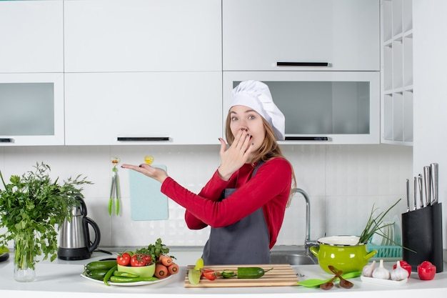 Front view wondered female chef in apron pointing at something