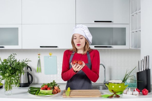 正面図はトマトを保持しているエプロンで女性料理人を不思議に思った