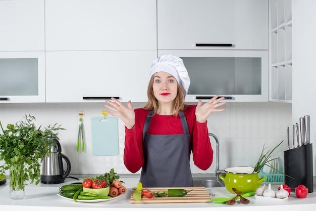 正面図は彼女の手を開くエプロンの女性料理人を不思議に思った