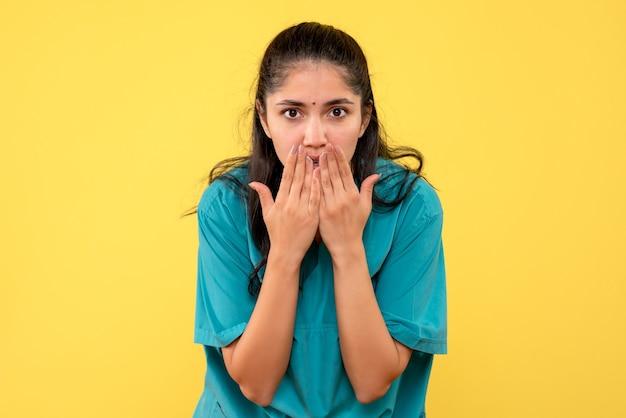Вид спереди удивился женщине-врачу в униформе, стоящей на желтом изолированном фоне