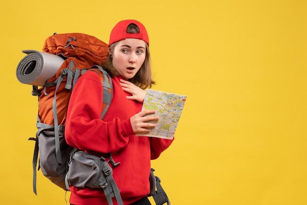 Вид спереди удивленная туристка с красным рюкзаком, держащая карту