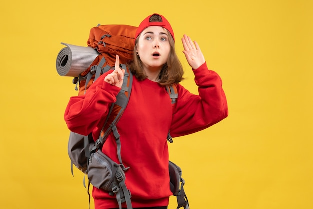 Front view wondered female traveler with backpack pointing finger up