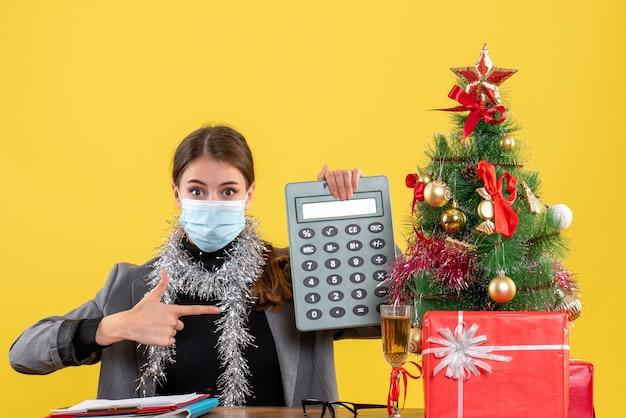正面図は、電卓のクリスマスツリーとギフトカクテルを保持しているテーブルに座っている医療マスクを持つ女の子を不思議に思った