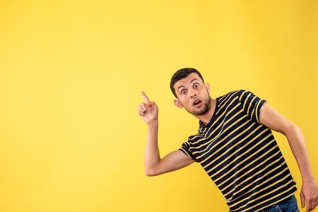 전면보기는 검은 색과 흰색 줄무늬 티셔츠 노란색 격리 된 배경 복사 장소에서 잘 생긴 남자를 궁금해