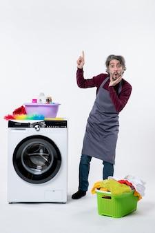 Вид спереди удивился экономке, стоящей возле корзины для белья стиральной машины на белой стене