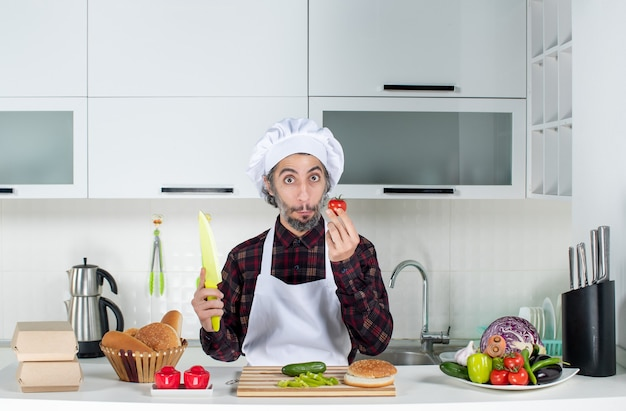 Front view of wondered male chef holding tomato and knife in the kitchen