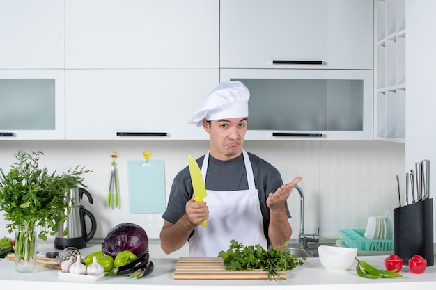 Front view wondered male chef in uniform holding knife in kitchen